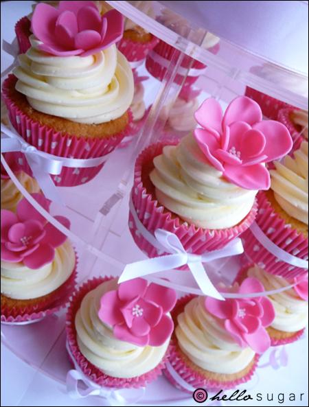 rosa cupcakes med sockerblommor och prickiga formar